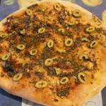 Passare uno spicchio di aglio sulla pizza cotta e spalmarla di pesto di olive