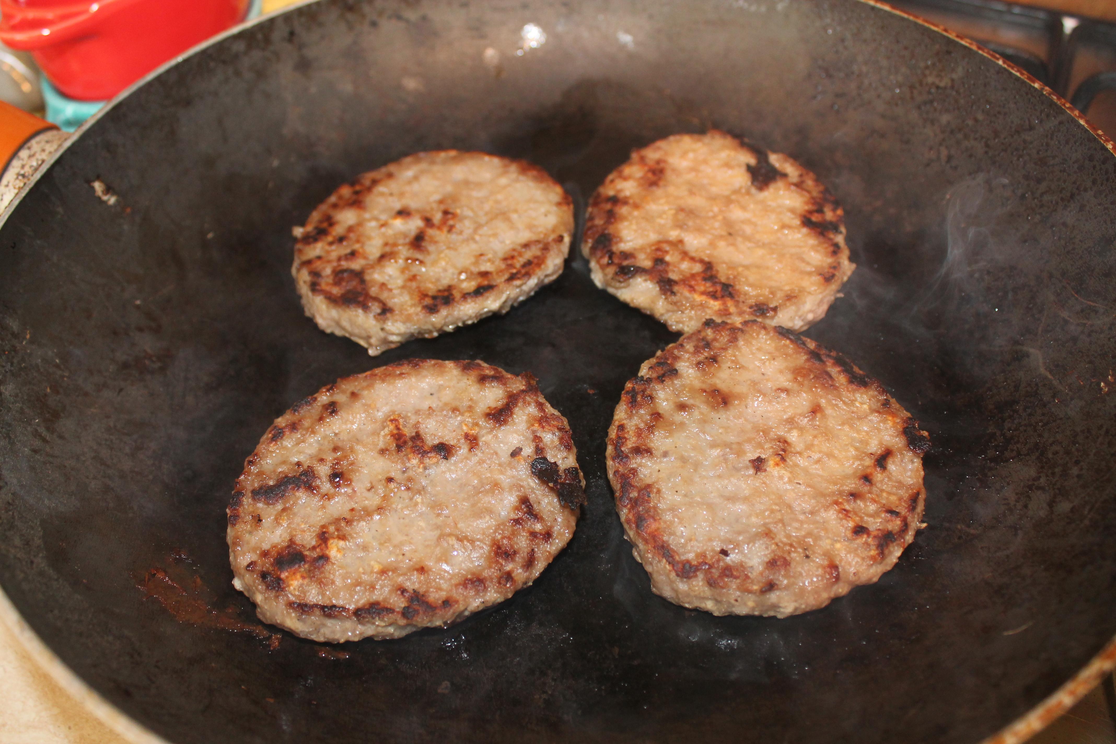 cuocere gli hamburger in una padella rovente senza condimenti appena saranno cotti abbassare al minimo la fiamma e ammassarli su un lato per tenerli in